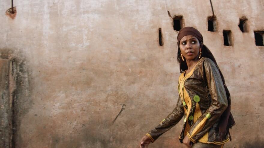 Jaha Dukureh walks down a street in Serrekunda, the sprawling urban area where she grew up in Gambia.