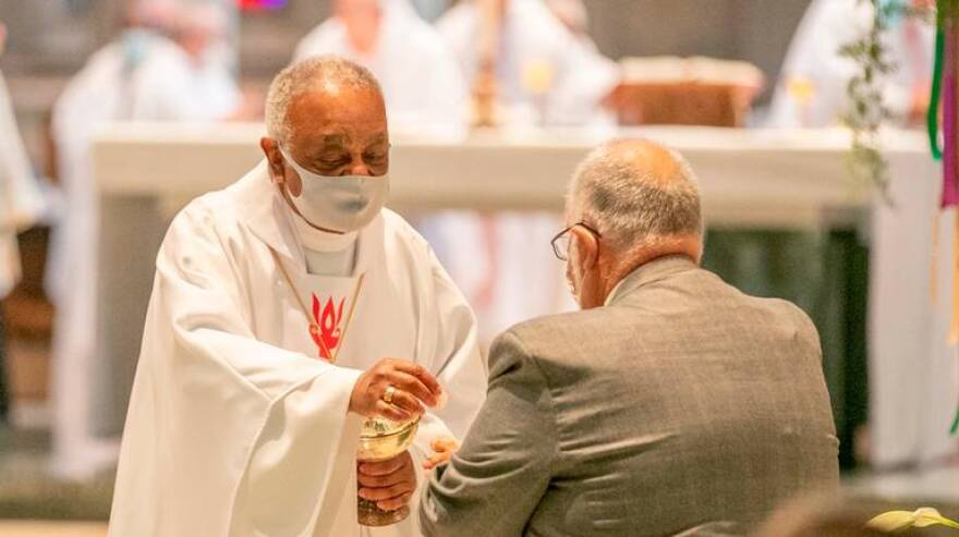 Archbishop Wilton D. Gregory, former bishop of the Catholic Diocese of Belleville, gives communion during a Mass of ordination and installation for new Bishop Michael G. McGovern at the Cathedral of St. Peter in Belleville in July.