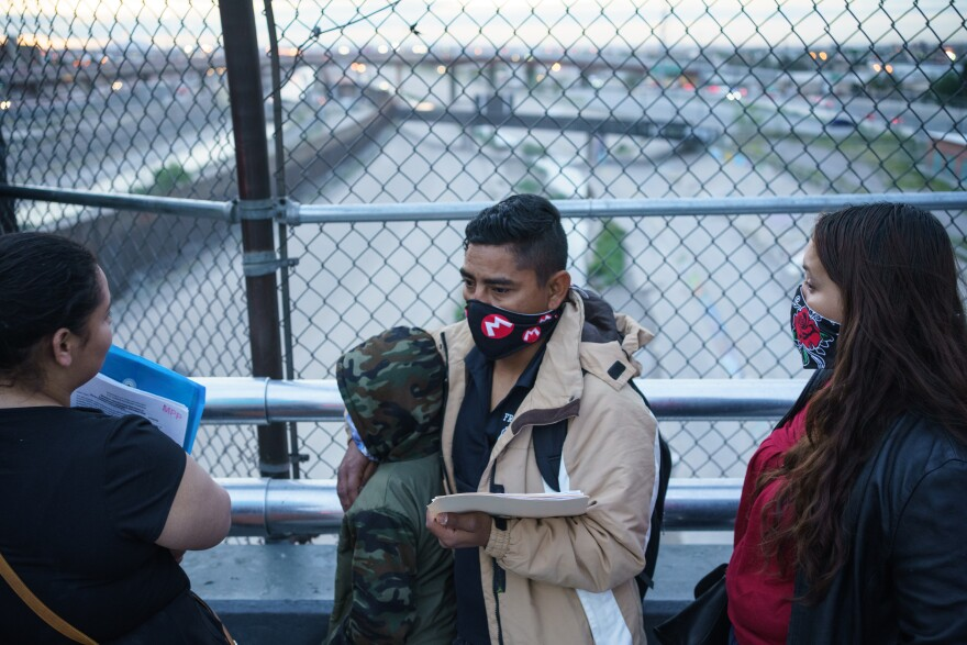 The Pinell family, husband and wife Cesar and Carolina and son Donovan, wait atop the Paso del Norte International Bridge.