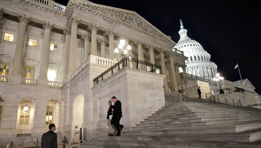 Congressmen walk down the steps of the House of Representatives as they work overnight on a spending bill in February.
