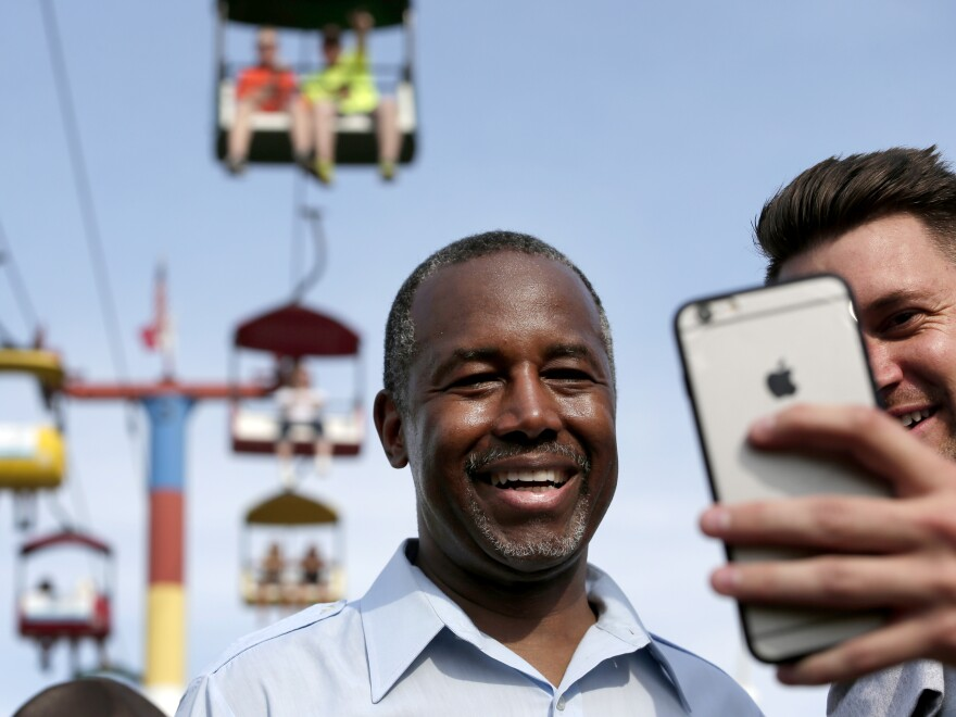 Ben Carson poses for a photo with a fairgoer at the Iowa State Fair in August.