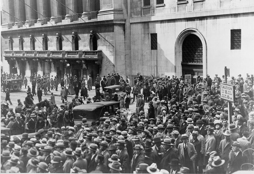 A photo of a crowd of people gather outside the New York Stock Exchange following the Crash of 1929.