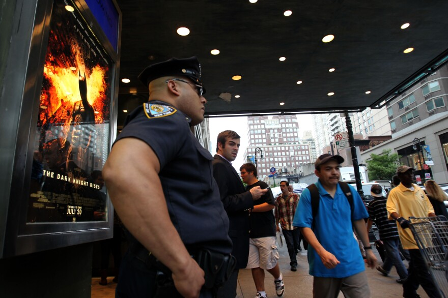 """A policeman stands outside a movie theater in New York on Friday during a showing of """"The Dark Knight Rises."""""""
