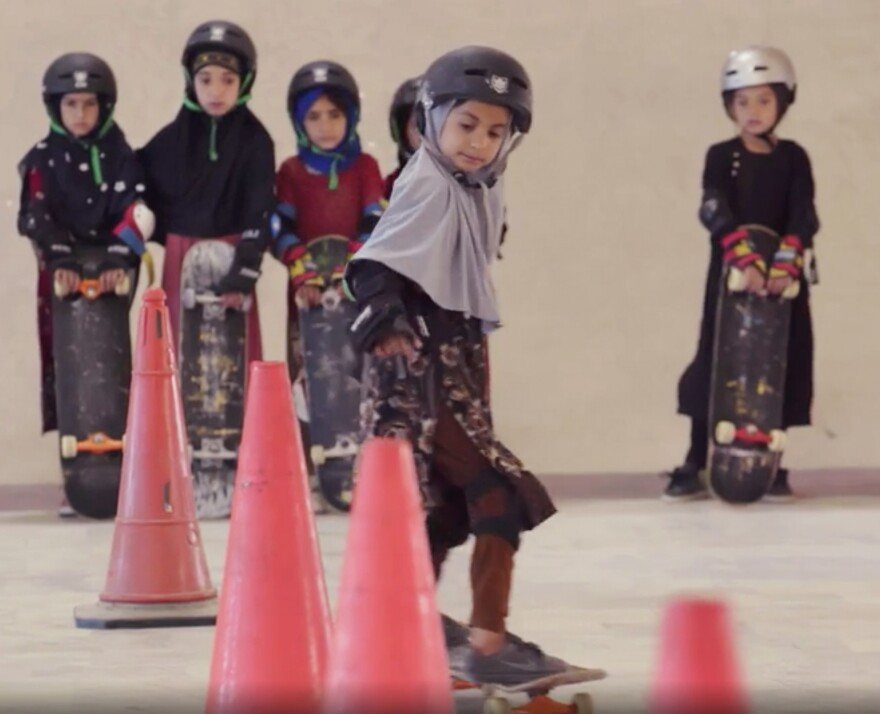 "Students wearing headscarves and helmets learn to navigate traffic cones in a scene from the Oscar-winning documentary, ""Learning to Skateboard in a Warzone (If You're a Girl)."""
