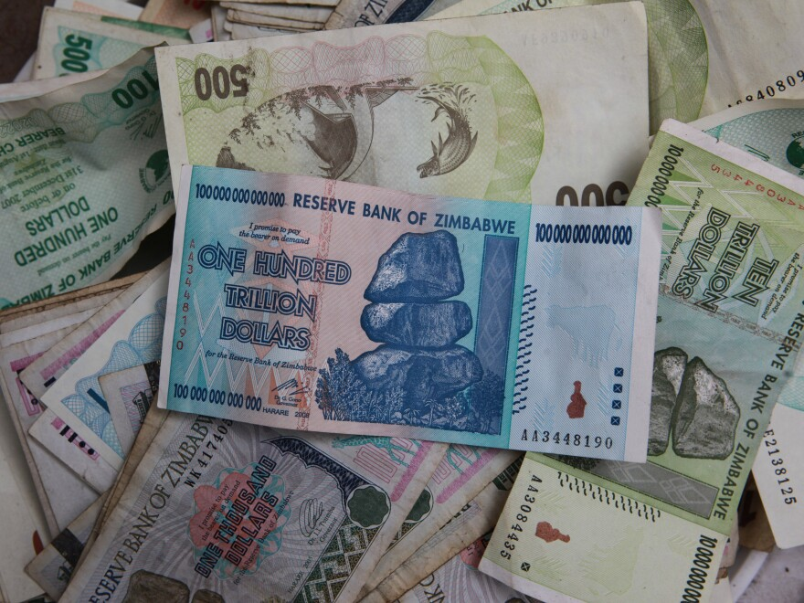 An old one hundred trillion Zimbabwean dollar note on top of a pile of other old Zimbabwean notes of various denominations in Harare, Thursday. Starting next week, Zimbabweans will be able to exchange their trillions for up to $5 U.S.