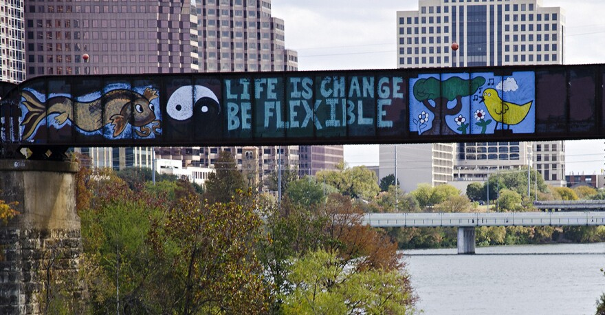 """A mural on the train bridge with the words """"Life is Change, Be Flexible"""" and a yin-yang symbol to the left."""