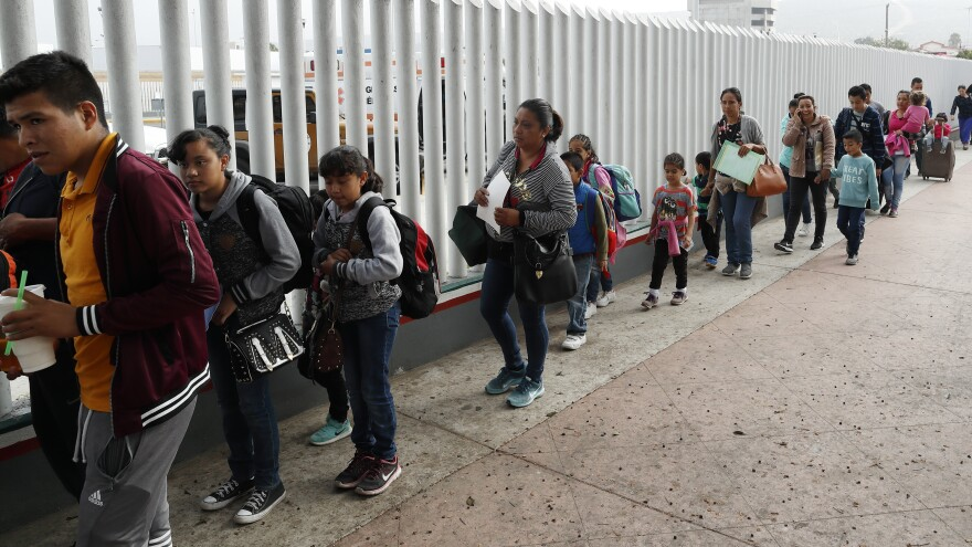 "People line up to cross into the United States to begin the process of applying for asylum near the San Ysidro port of entry in Tijuana, Mexico. Homeland Security's watchdog says immigration officials were not prepared to manage the consequences of its ""zero tolerance"" policy at the border."
