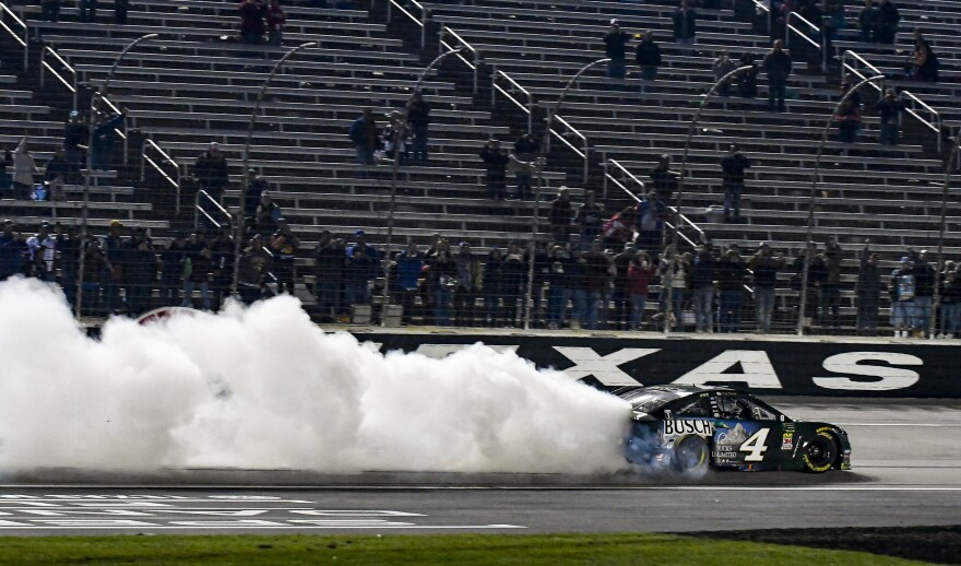 A car makes a trail of white smoke in front of mostly empty grandstands.