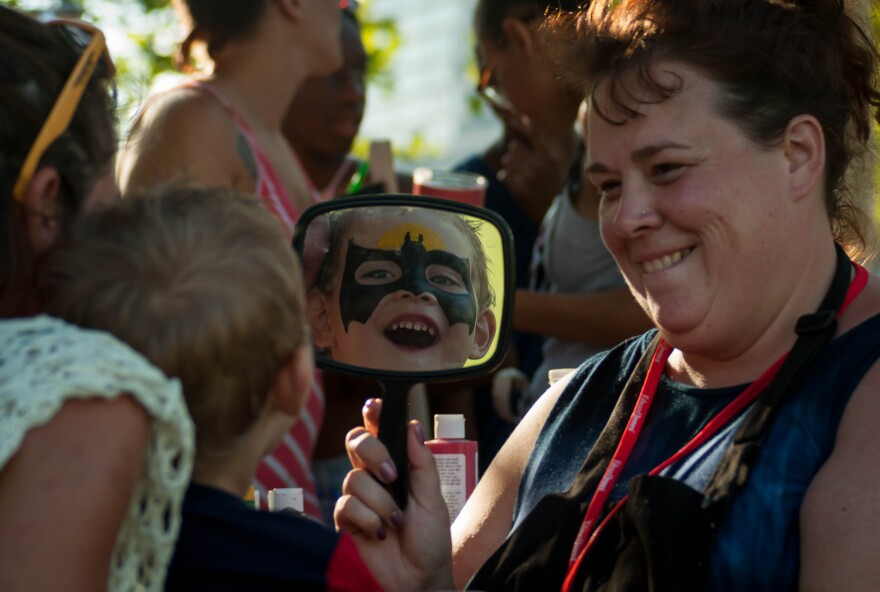 Mason Kidwell, 3, inspects himself in the mirror as Batman by face-painter Rhiannan Gurley at Fair St. Louis Wednesday, July 4, 2018.
