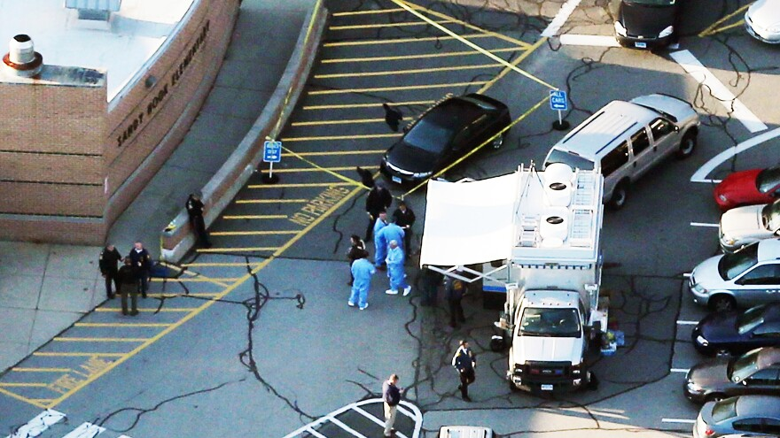 Police and medical staff work outside Sandy Hook Elementary School in Newtown, Conn., where 27 people — 20 of them children — were killed Friday morning. Police have not officially declared a suspect, but news accounts have named Adam Lanza, 20, as the suspected gunman.