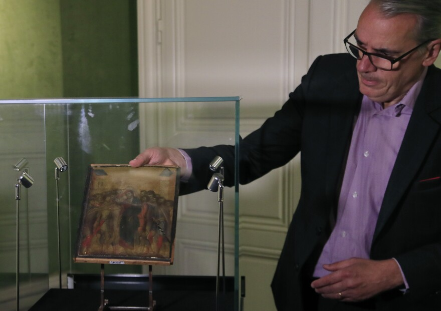 Art expert Stéphane Pinta takes out of a glass case a 13th century painting by Italian master Cimabue in September. That painting, sold for nearly $27 million, is now the subject of a power struggle between an art buyer and the government of France.
