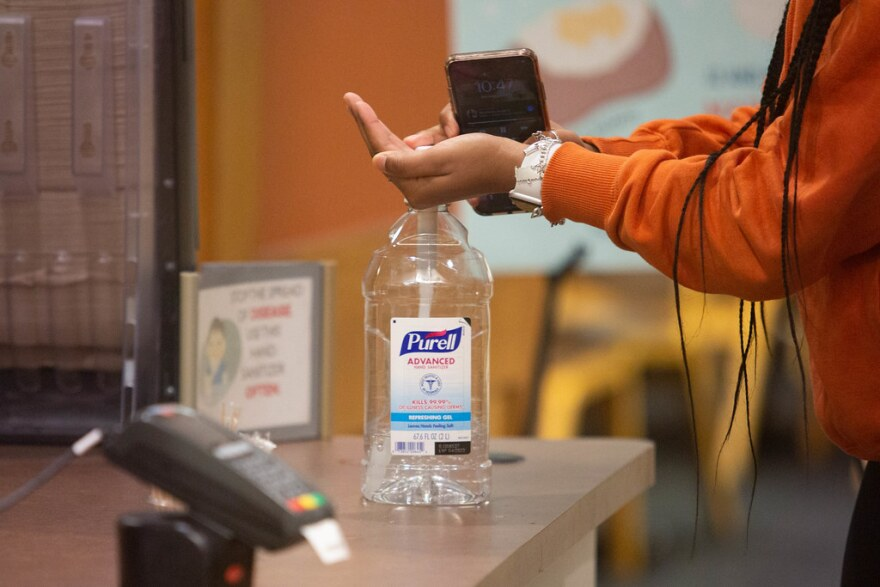 A person uses hand sanitizer.