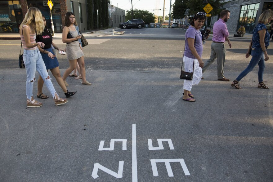 people walking on an austin street across a line marking different political districts