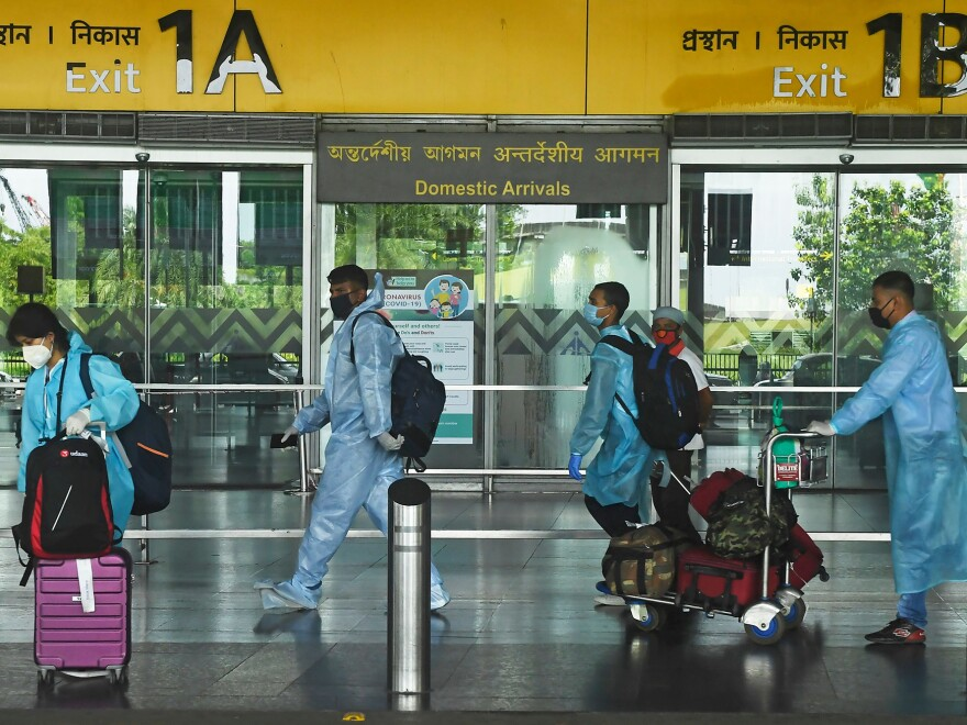 Air passengers wearing practically full-body coveralls at the Netaji Subhas Chandra Bose International Airport in India.