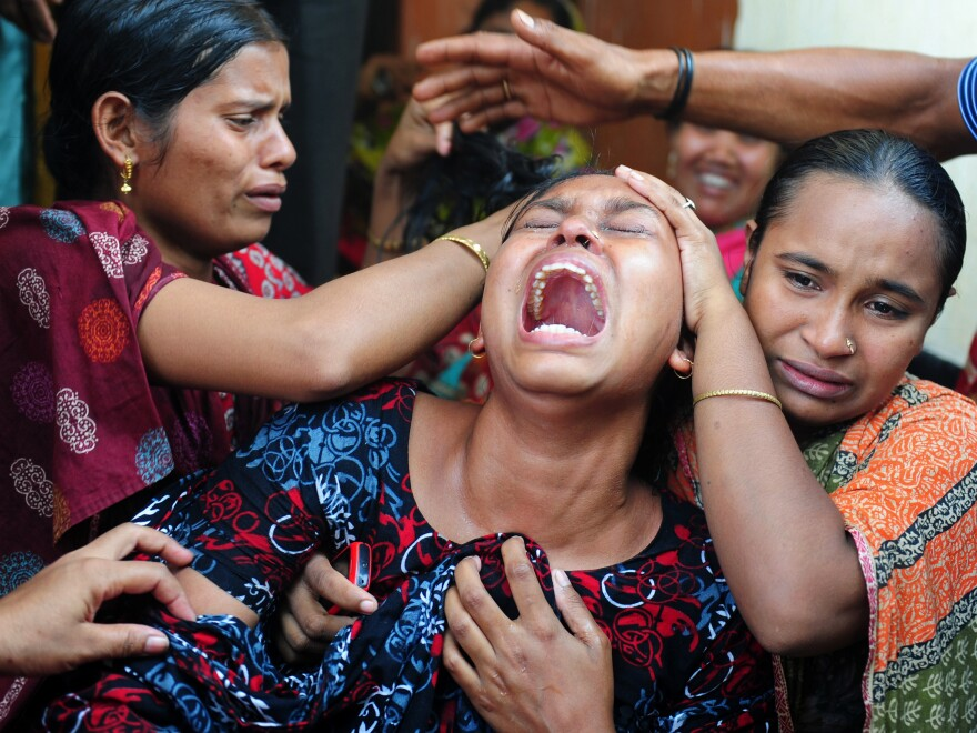 Relatives react after identifying the body of a loved one who was killed in last week's building collapse in Savar, on the outskirts of Dhaka, Bangladesh.