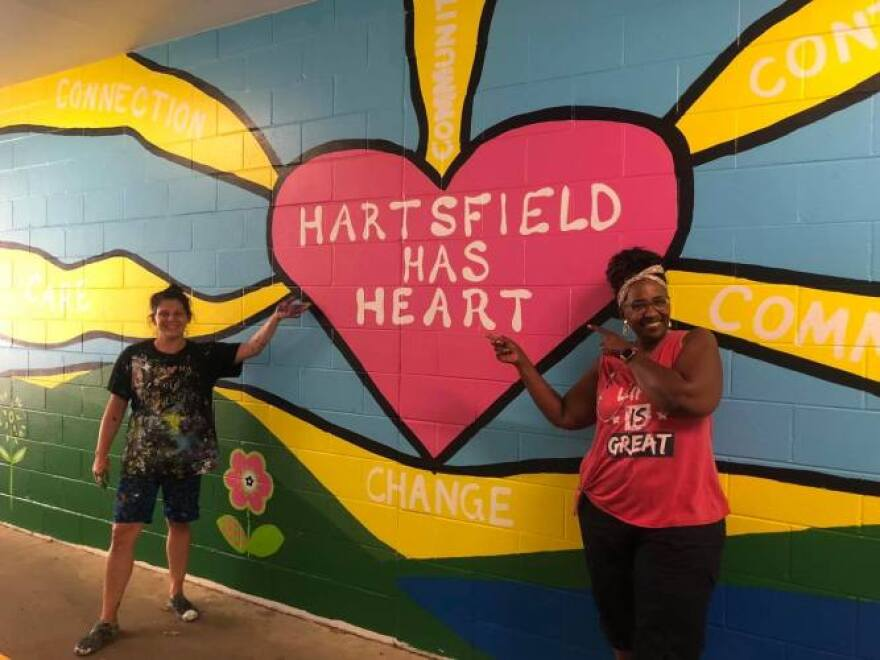 """Two Hartsfield Elementary School teachers smile and point to a multicolor wall mural that says """"Hartsfield Has Heart"""" written inside a heart shape."""