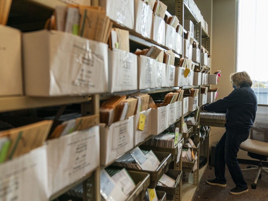 An election worker organizes absentee ballots ahead of Election Day at the city clerk office in Warren, Mich.