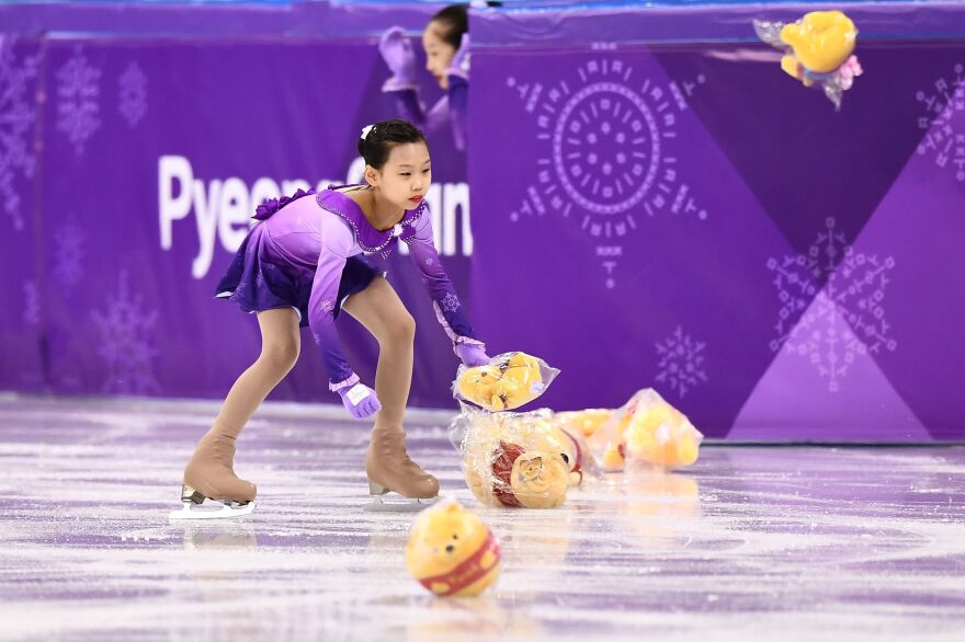 "A ""flower girl"" collects Winnie the Pooh stuffed animals thrown by fans of Japanese gold medalist figure skater Yuzuru Hanyu on Feb. 16, during the men's figure skating short program."