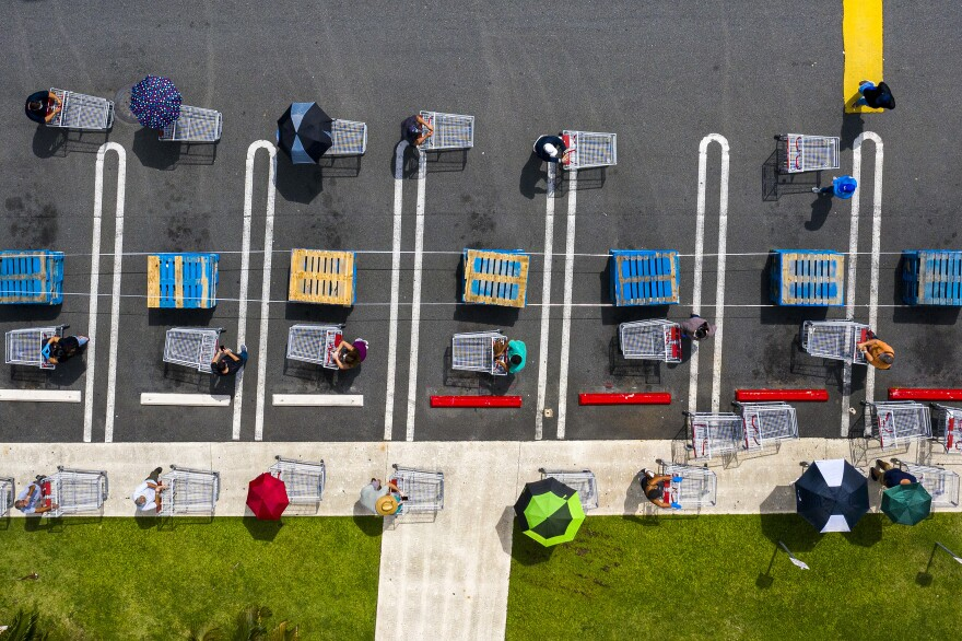 People keep their distance as they wait in line at a retail store in Carolina, Puerto Rico.