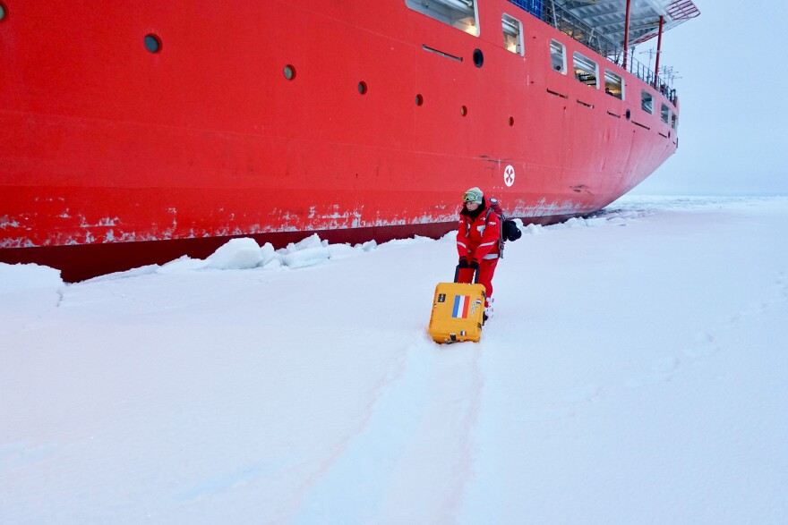 Scientist Jessie Creamean moves a portable aerosol sampler out onto the ice to test it in the cold conditions.