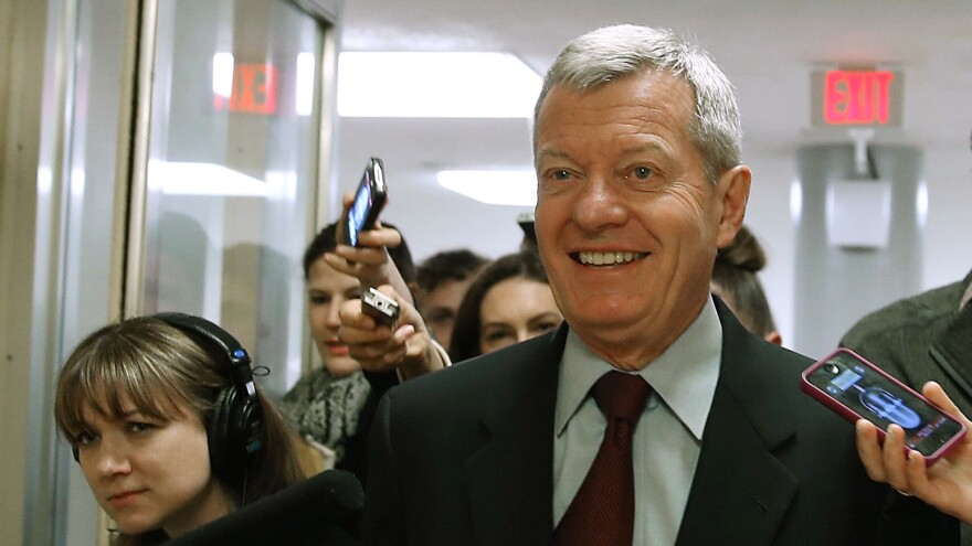 Sen. Max Baucus, D-Mont., is trailed by reporters Monday on Capitol Hill after announcing that he'll retire in 2014.
