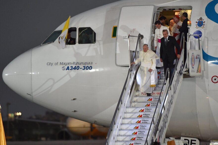 """Pope Francis disembarks from the plane upon his arrival at the airport in Manila, Philippines, on Wednesday. In comments to reporters aboard the plane, Francis said though the attack on <em>Charlie Hebdo</em> magazine was an """"aberration,"""" free speech """"cannot make provocations,"""" especially against people's faith."""