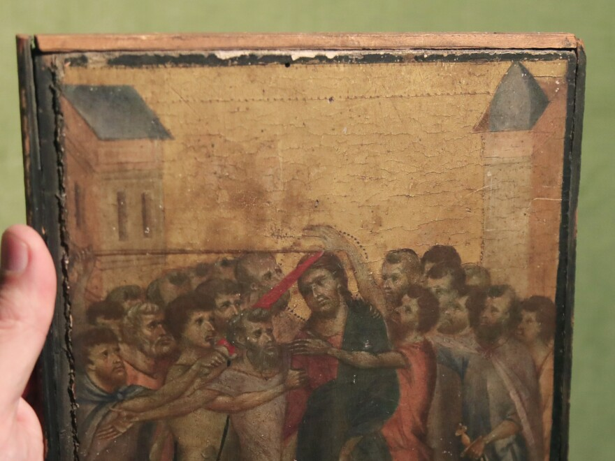 Art expert Stéphane Pinta points to a 13th century painting by Italian master Cimabue in Paris.