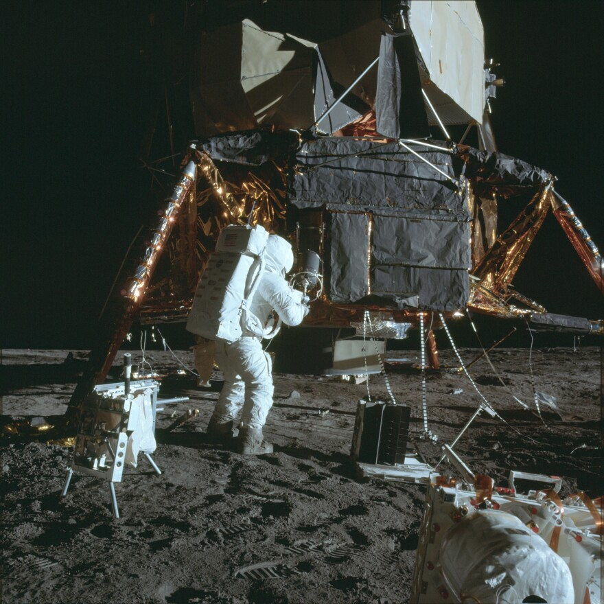 Astronaut Al Bean removing an experiment at the landing site for Apollo 12 in November 1969.