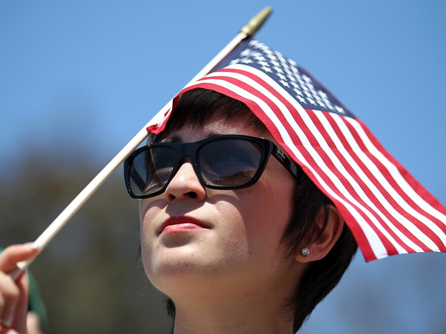 A supporter of Republican Mitt Romney holds an American flag as he speaks during a Memorial Day tribute at the Veterans Museum & Memorial Center in San Diego.