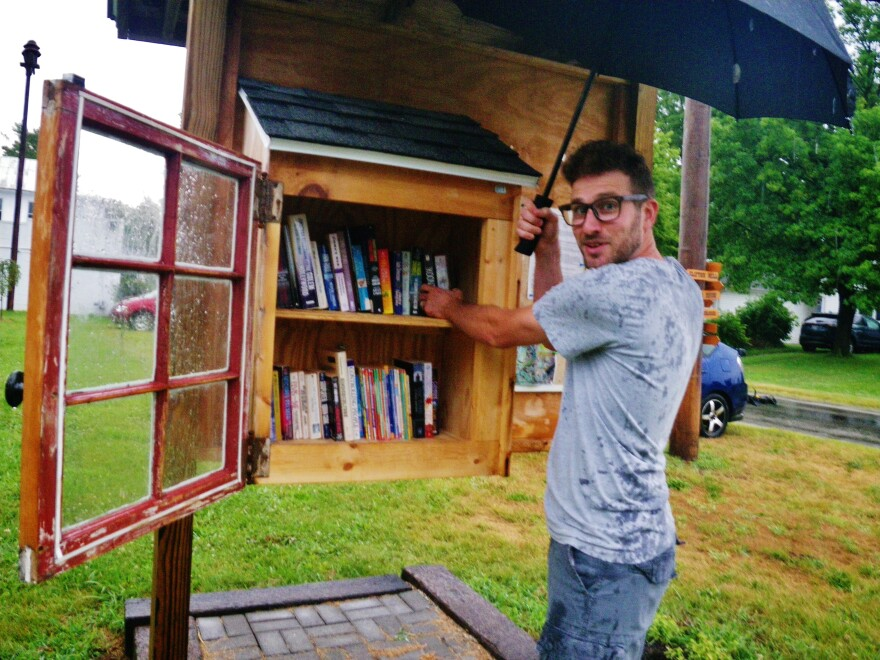 Ryan Ireland restocks a Little Free Library on a rainy day in Clifton.