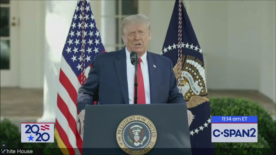 Man in suit and tie standing at podium with flags behind him