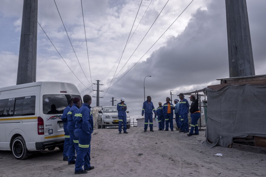 A group of janitors, standing in a parking lot, say they lack the cleaning products needed to take care of communal toilets in the township of Khayelitsha. Each public toilet is used by dozens of people every day.