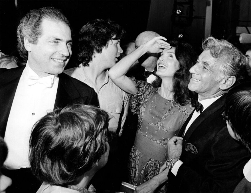 """Jacqueline Kennedy Onassis shields the light from her eyes as she looks up at the stage at the John F. Kennedy Center for the Performing Arts.  With her is conductor-composer Leonard Bernstein, who wrote """"Mass"""" for the opening of the cultural center. (AP)"""
