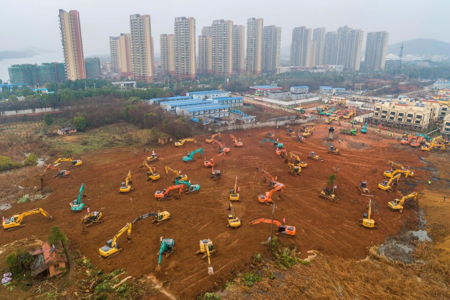 Excavators are seen at the construction site of a medical center being built in Wuhan, China, to treat patients of the coronavirus outbreak. Ground was broken on Jan. 24. According to Chinese state media, the facility opened on Feb. 3.