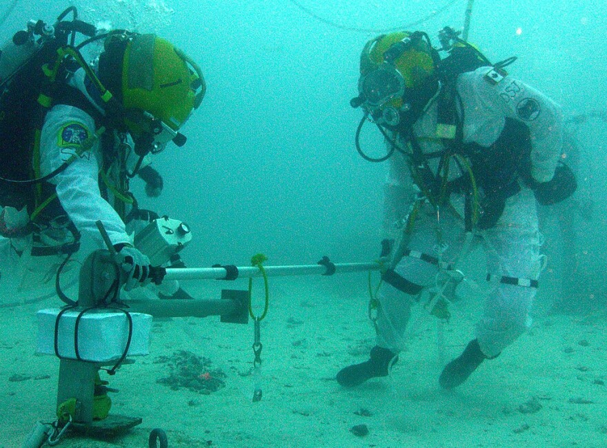 Astronauts Shannon Walker and David Saint-Jacques test a probe in the waters off Key Largo, Fla. Their research may help NASA set foot on an asteroid someday.
