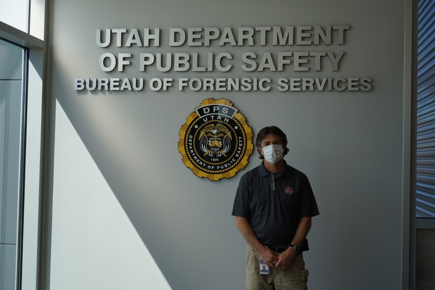 """Photo of a man standing in front of a sign that reads """"Utah Department of Public Safety: Bureau of Forensic Services."""""""