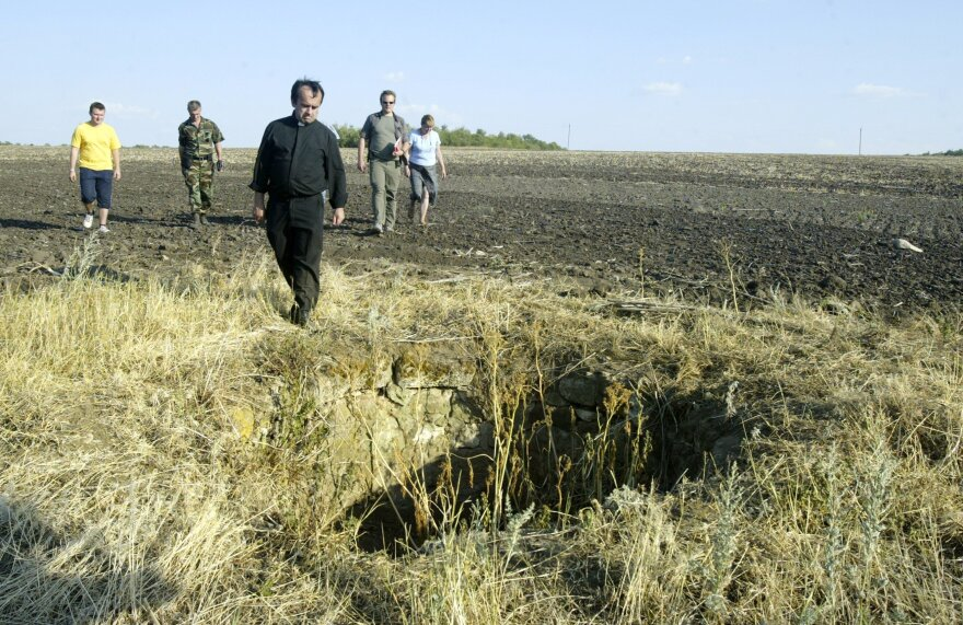 Desbois and members of his team walk to what used to be a well in Bogdanovka, Ukraine, in 2007. During the Holocaust, many Jews were thrown into the well dead or still alive. Over a period of three weeks in late December 1941 and early January 1942 — with a break for Christmas — 48,000 Jews were executed in Bogdanovka.