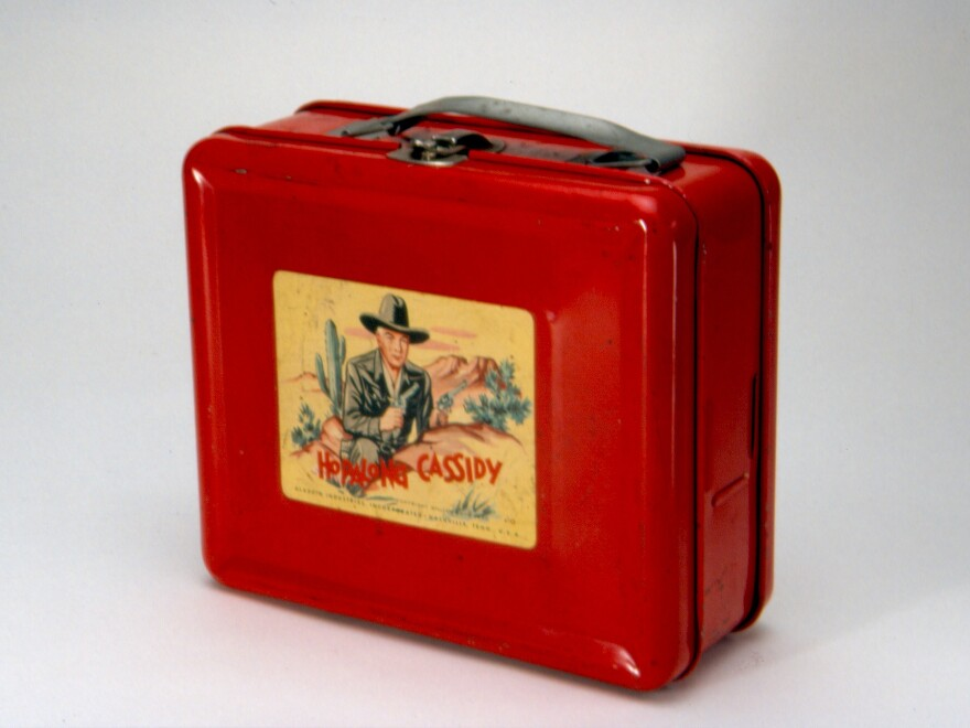 This steel lunch box, made by Aladdin Industries in 1950, was the first to bear a licensed image, and helped Aladdin launch a new product line that would last for decades. <em>Hopalong Cassidy</em> was a popular TV, radio and comic series.