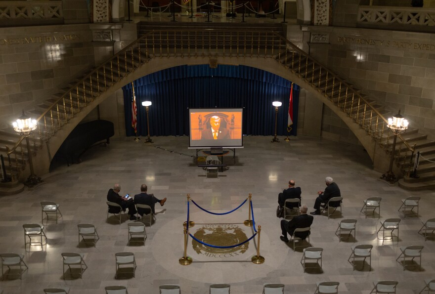 A small group of people watch Governor Mike Parson during his State of the State address on a screen set up in the Rotunda of the Missouri State Capitol Building that was set up as an overflow area on Wednesday, January 27, 2021, in Jefferson City