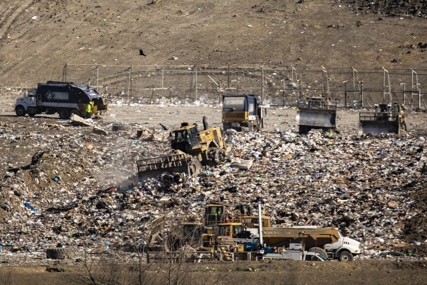 Trucks move trash in the Austin Community Landfill off Highway 290.