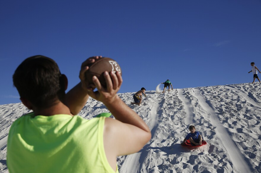 Families play on the dunes. 