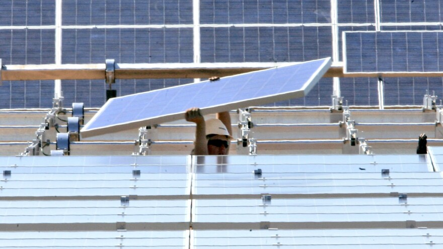 A solar energy panel is lifted into place in a solar energy field at the Sacramento Municipal Utility District in Rancho Cordova, Calif.