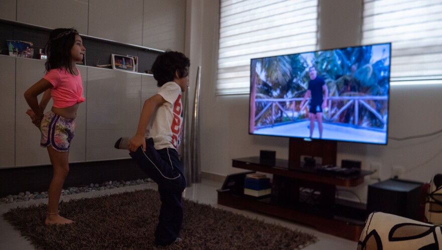 Ivanna and Alonso Granados exercise in their living room through a televised PE class that's part of the Mexican Government's at-home learning program.