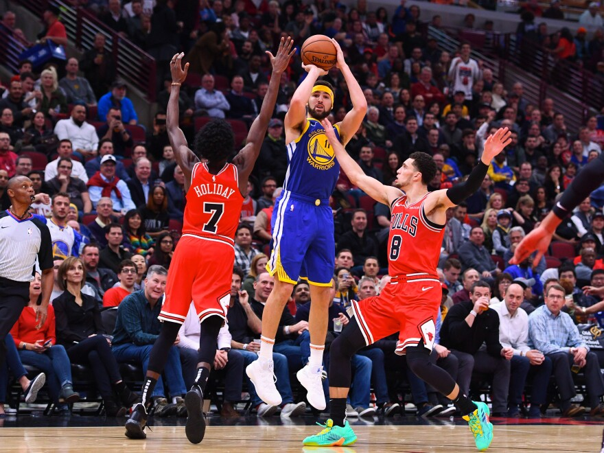 Golden State Warriors guard Klay Thompson shoots the ball against Chicago Bulls forward Justin Holiday (7) and guard Zach LaVine (8) during Monday night's game. Thompson broke the NBA's single-game record for 3-pointers.