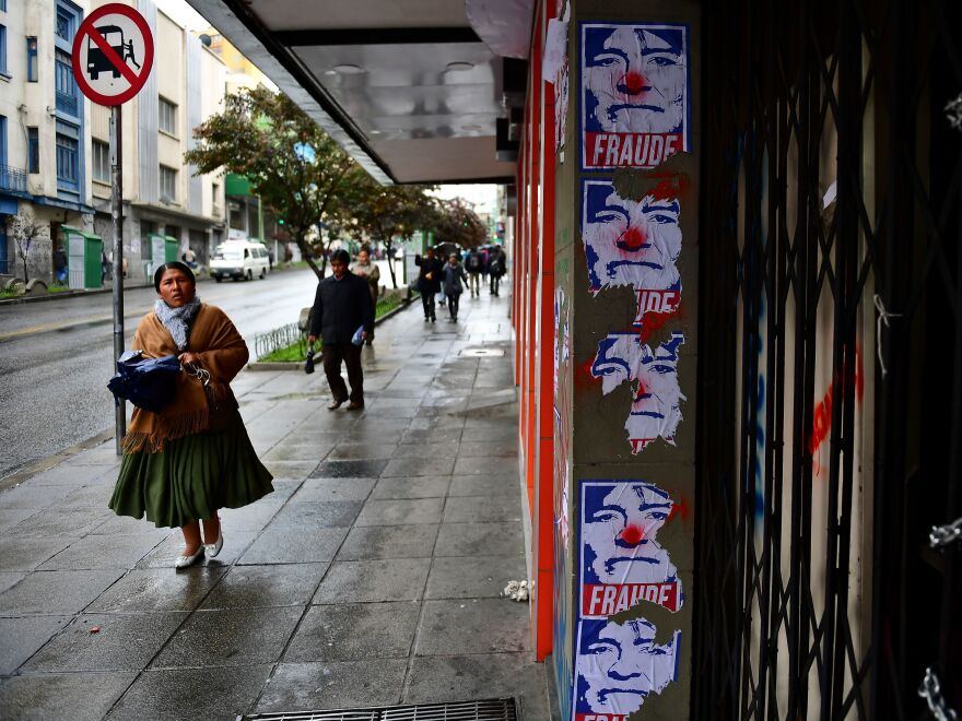 A woman walks past posters depicting Bolivian ex-President Evo Morales as a clown and a fraud in La Paz on Monday.