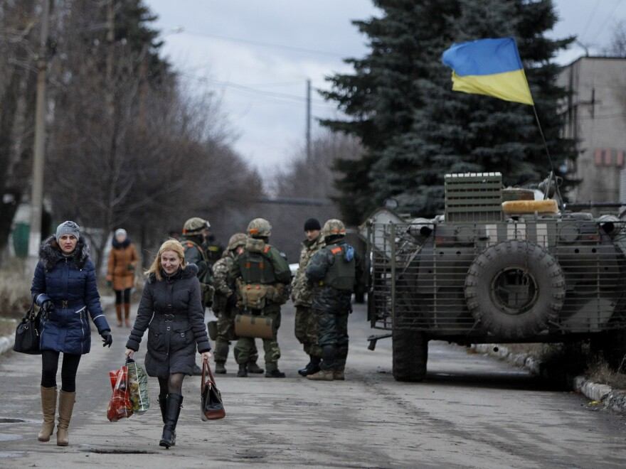 Women pass by a group of the Ukrainian government soldiers in the village of Debaltseve, Donetsk region, eastern Ukraine on Wednesday. Peace talks to resolve the conflict have inexplicably been called off.
