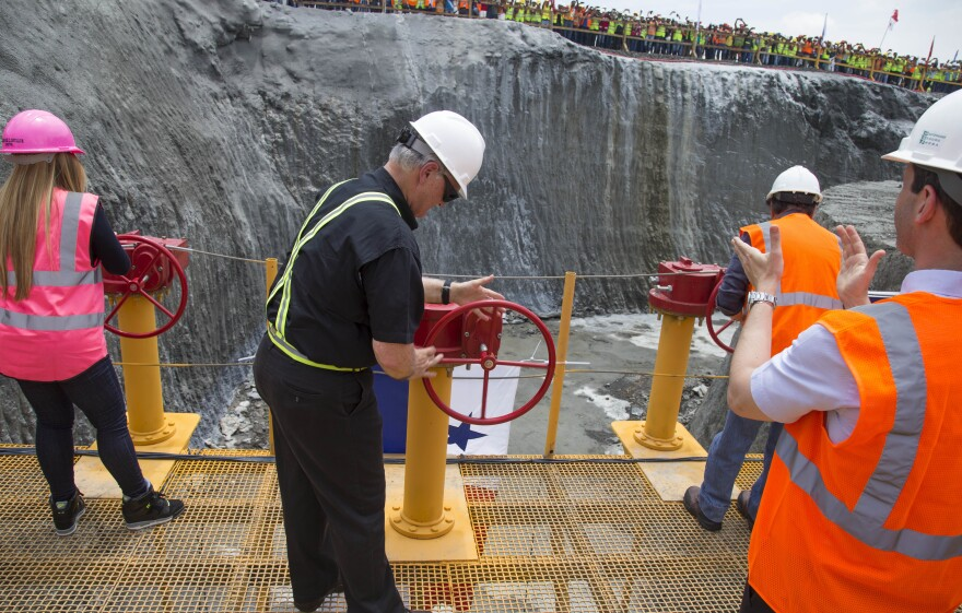 The head of the Panama Canal Authority, Jorge Quijano, center, opens the main valve to allow water into the flood chambers on the new set of locks on the Atlantic side of the Panama Canal in June 2015. The expansion of the canal, making it wider and deeper to accommodate larger ships, has taken nearly a decade. It opens next month.