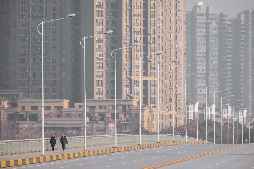 People walk down a deserted street in Wuhan, epicenter of the coronavirus outbreak, on Tuesday. Wuhan has gradually shut down all transportation channels for entering and leaving the city — no flights, trains, buses or boats.