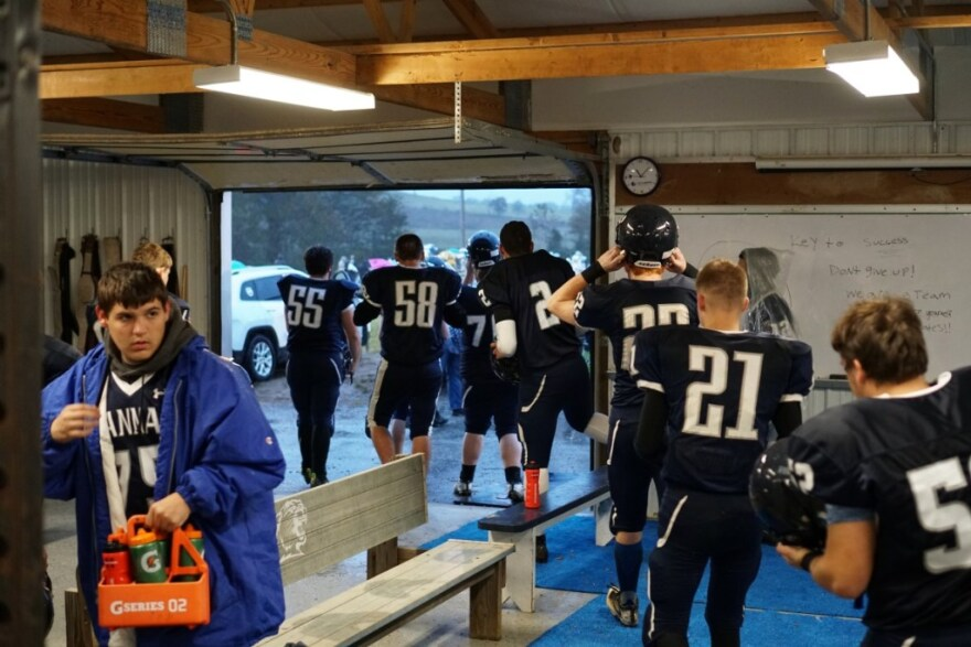 Hannan players pour out of their small locker room, ready to take the field.