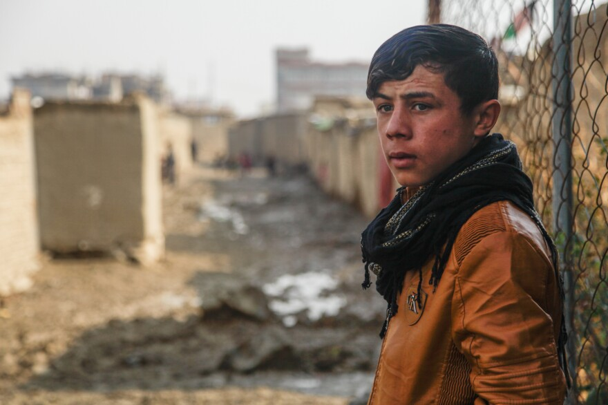 Shaista's 15-year-old son looks out onto a muddy alleyway on the outskirts of Kabul. He began selling firewood this year to help out his family after his father was injured in an accident.